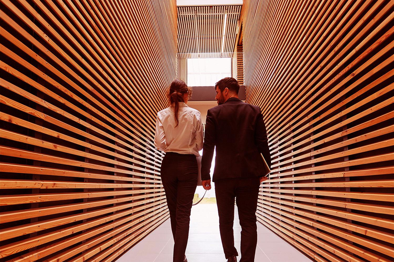 man and woman walking through hallway